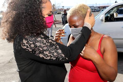 Kenya Young, 39, right, is comforted by friend Jazzmen Hicks during Young's coat drive in Histo ...