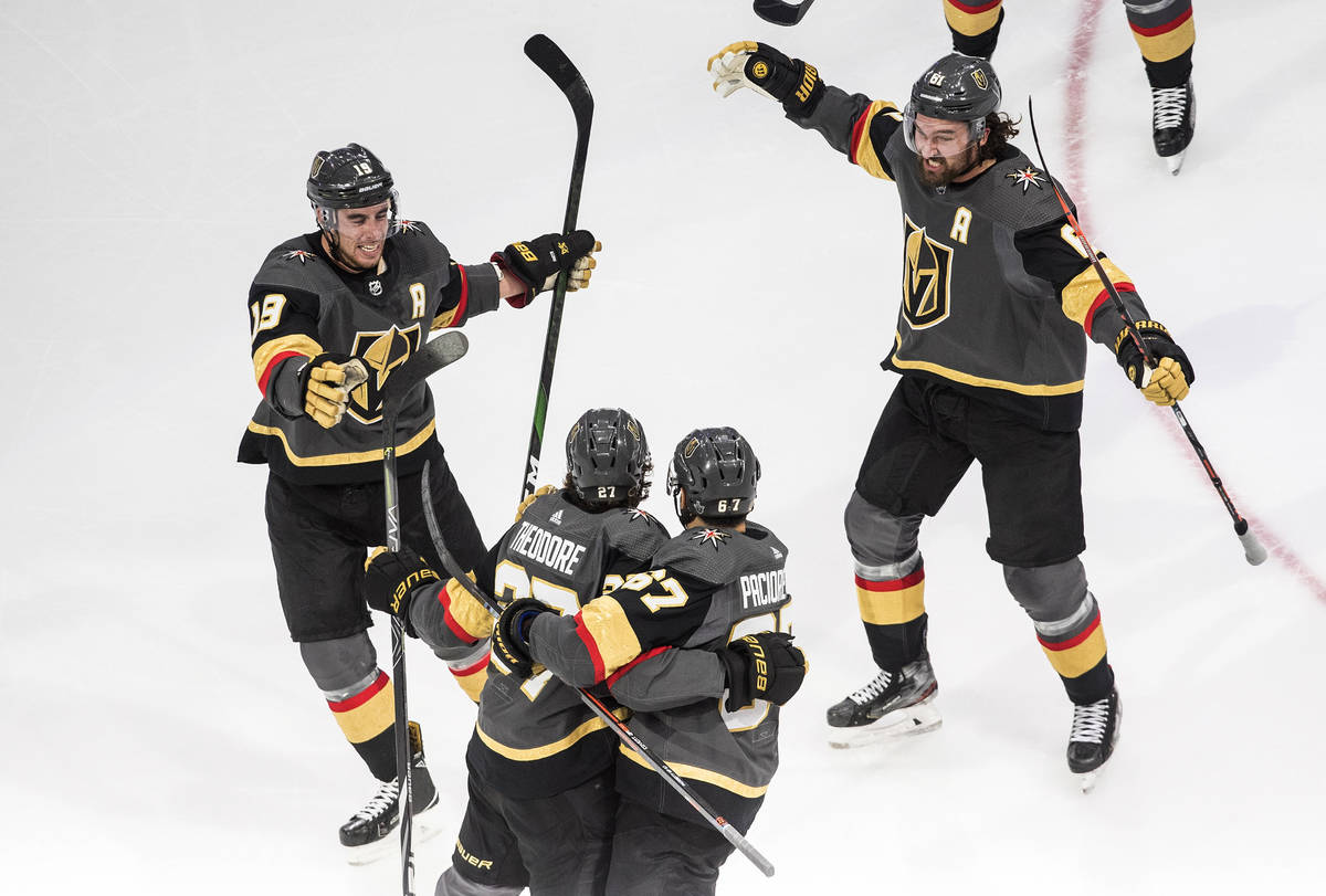 Vegas Golden Knights' Shea Theodore (27) celebrates his goal against the Vancouver Canucks with ...