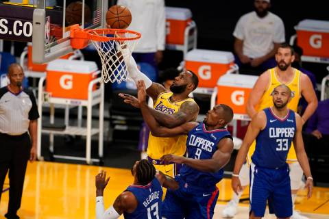 Los Angeles Lakers forward LeBron James, top, drives to the basket over Los Angeles Clippers ce ...