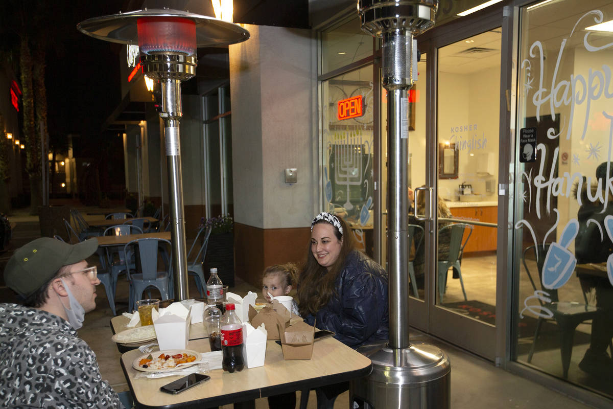 Avi Weiss, left, Sara Weiss, 4, and Julie Weiss, of New York, dine outdoors at Kosher Chinglish ...