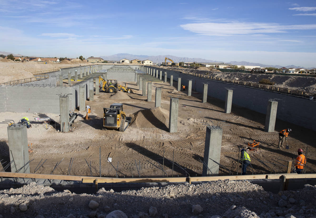 Construction workers at an underground parking garage at the Evora apartment complex site where ...