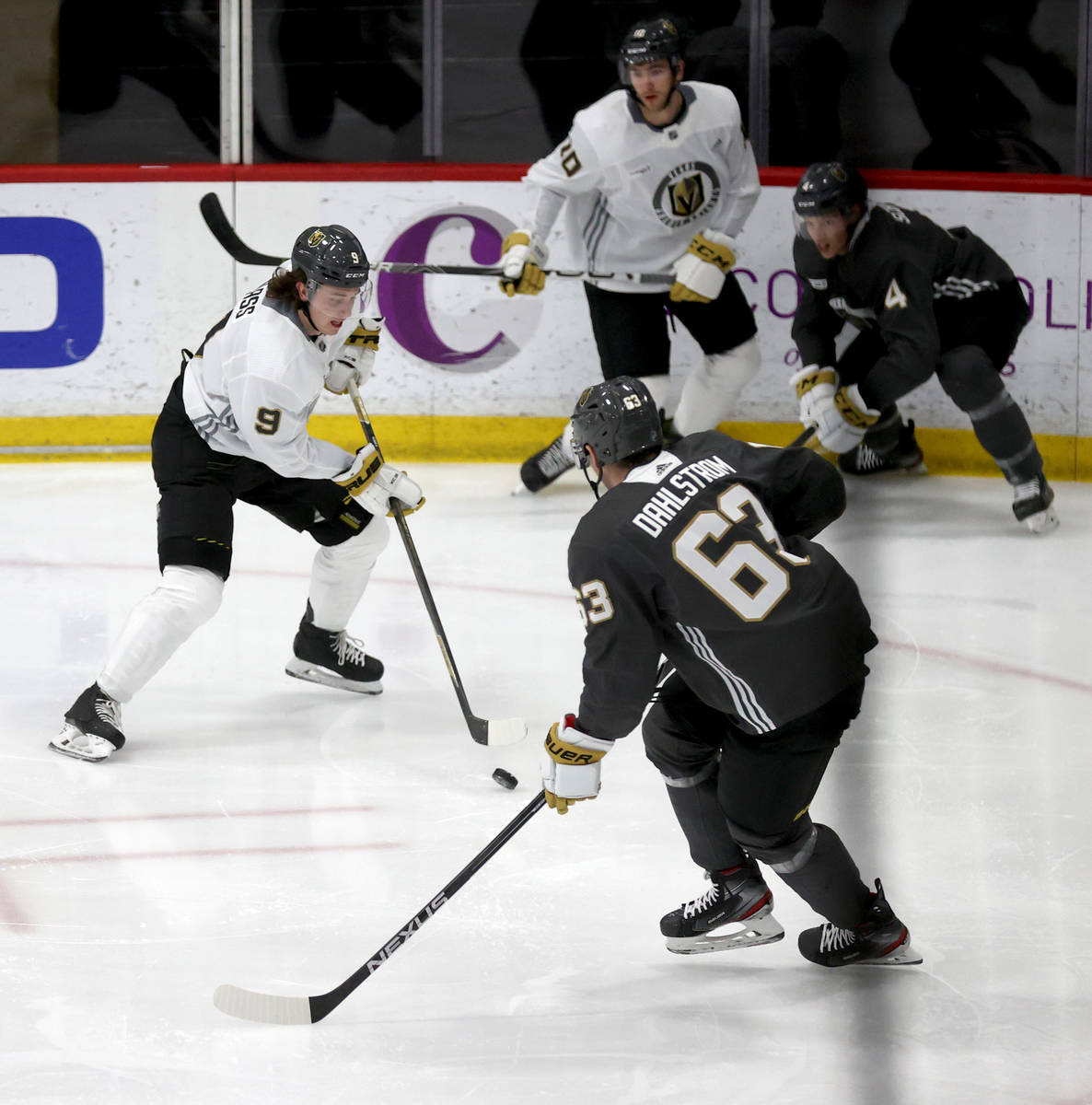 Golden Knights center Cody Glass (9) looks to move the puck past defenseman Carl Dahlstrom (63) ...