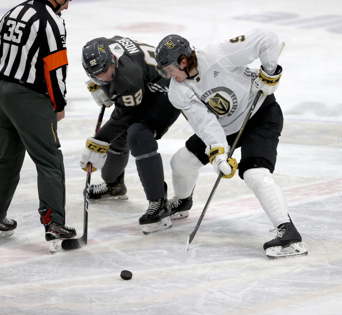 Golden Knights center Cody Glass (9) faces off against Golden Knights center Tomas Nosek (92) d ...