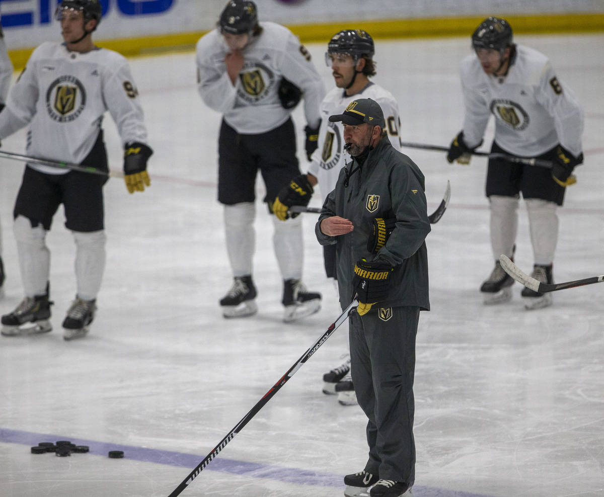 Golden Knights head coach Pete DeBoer blows his whistle as players look on during training camp ...