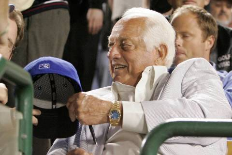 Former Los Angels Dodger coach Tommy Lasorda signs autograph as the Seattle Mariners take on th ...