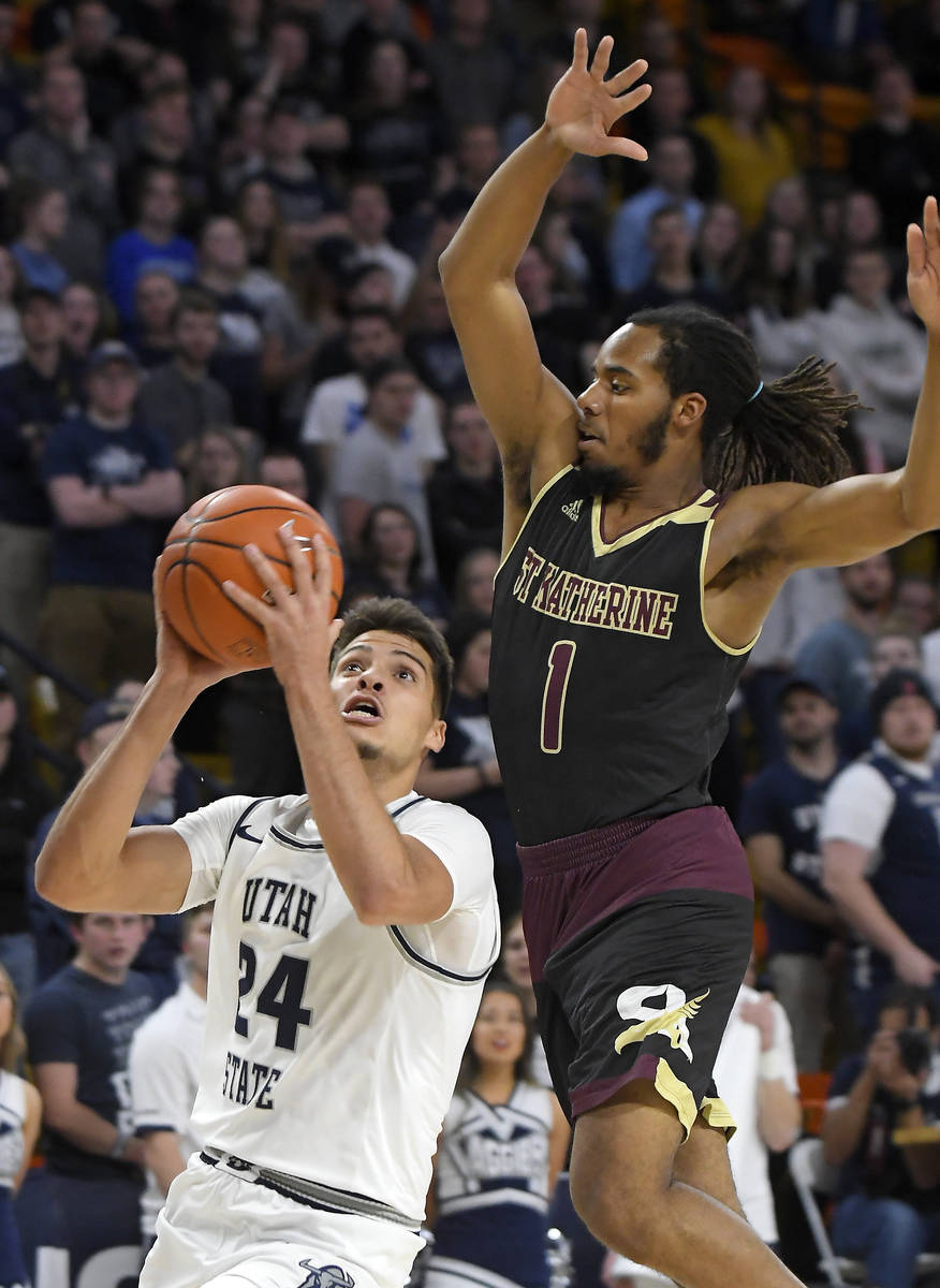 Utah State guard Diogo Brito (24) takes a shot as Saint Katherine's Austin Armstead (1) defends ...
