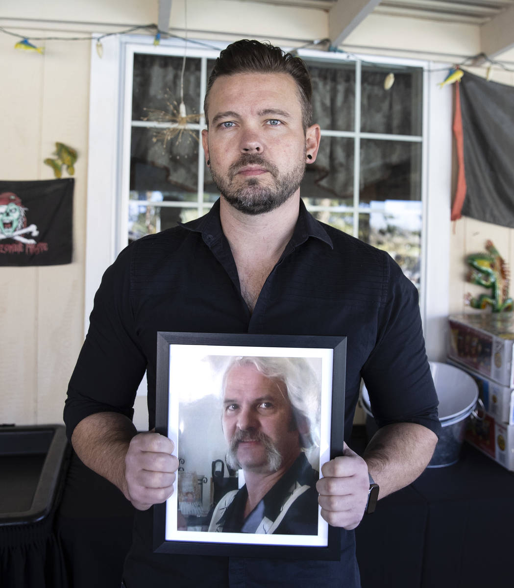 Ethan Bondelid, 40, holds his slain father, Alan Bondelid, 70, photograph at his father's Las V ...