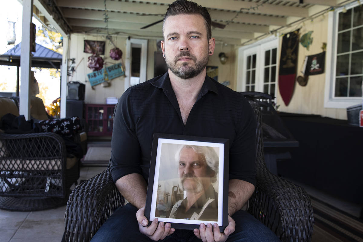 Ethan Bondelid, 40, holds a photograph of his slain father, Alan Bondelid, 70, at his father's ...