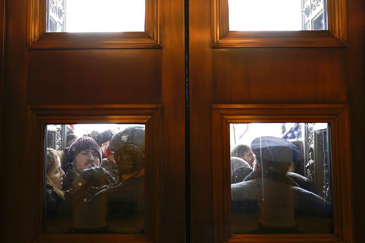 U.S. Capitol Police try to hold back rioters outside the east doors to the House side of the U. ...
