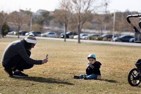 Lindsey Daub tries to get her 13-month-old son's, Luke, attention as she takes a picture of him ...