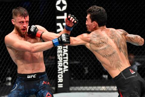 (R-L) Max Holloway punches Calvin Kattar in a featherweight bout during the UFC Fight Night eve ...