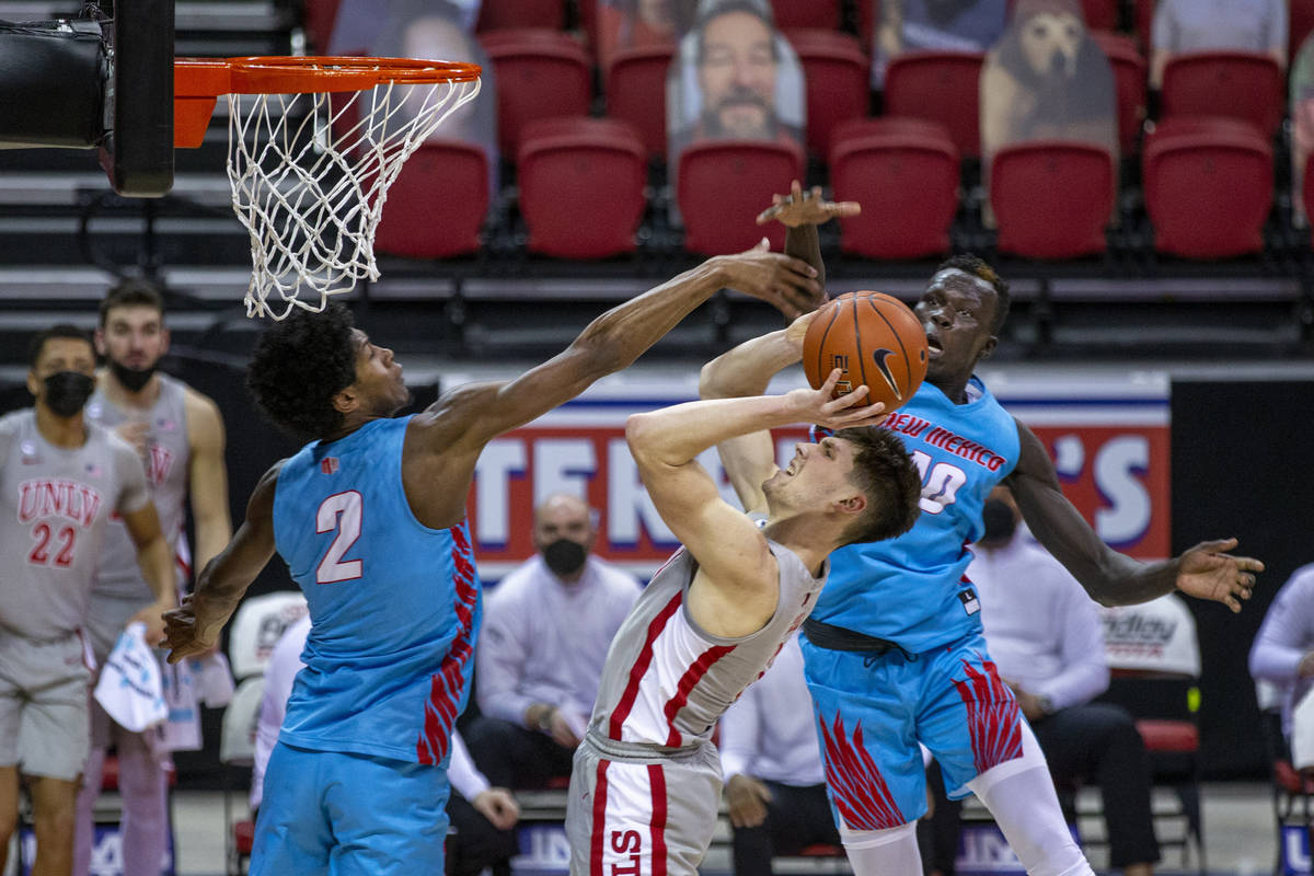 UNLV Rebels guard Caleb Grill (3) leans back to get off a basket between New Mexico Lobos guard ...