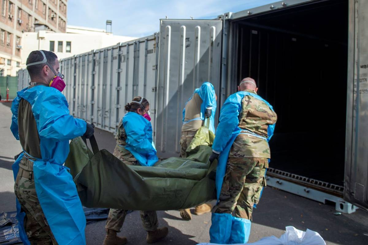 National Guard members assisting with processing COVID-19 deaths and placing them into temporar ...