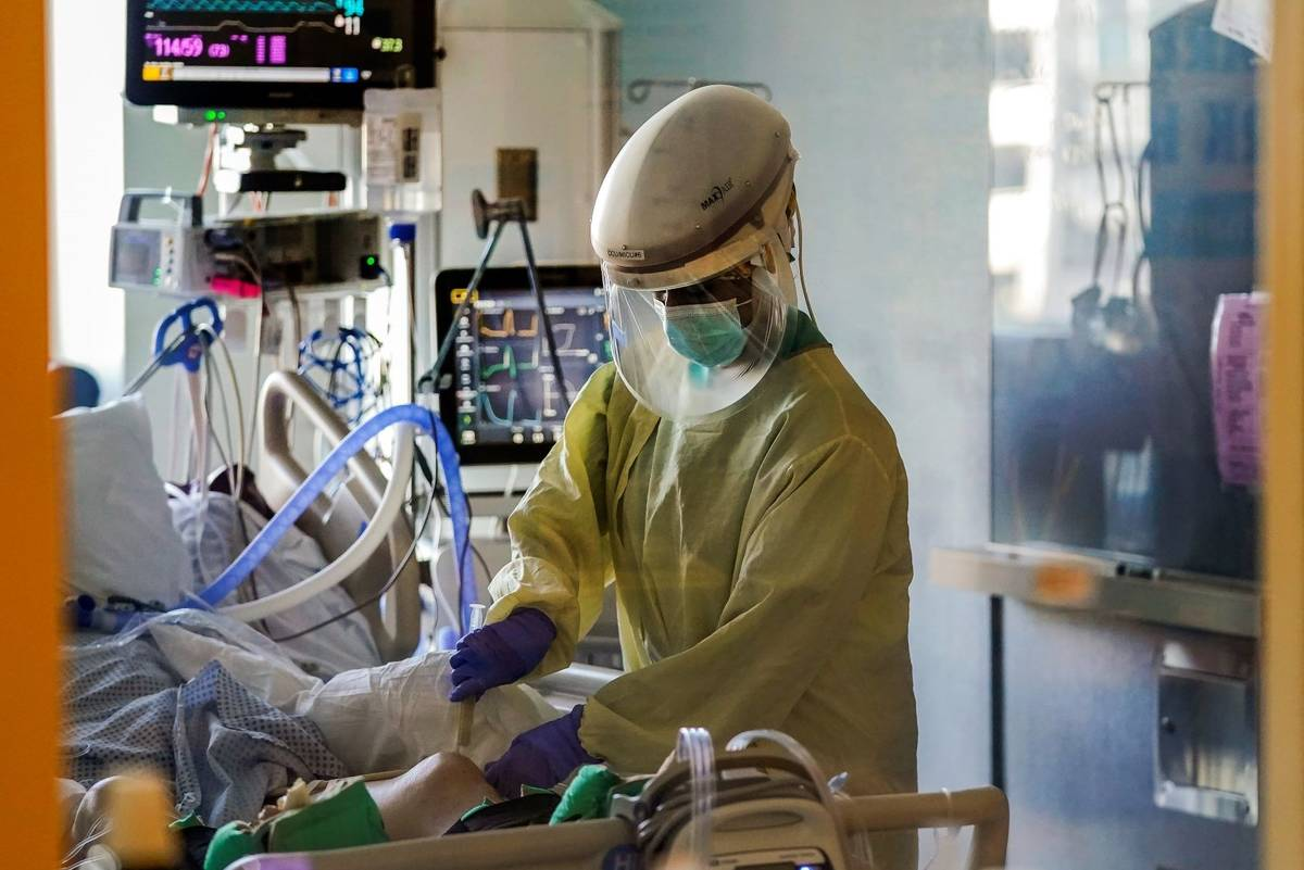 A healthcare worker tends to a COVID-19 patient in the intensive care unit at Santa Clara Valle ...