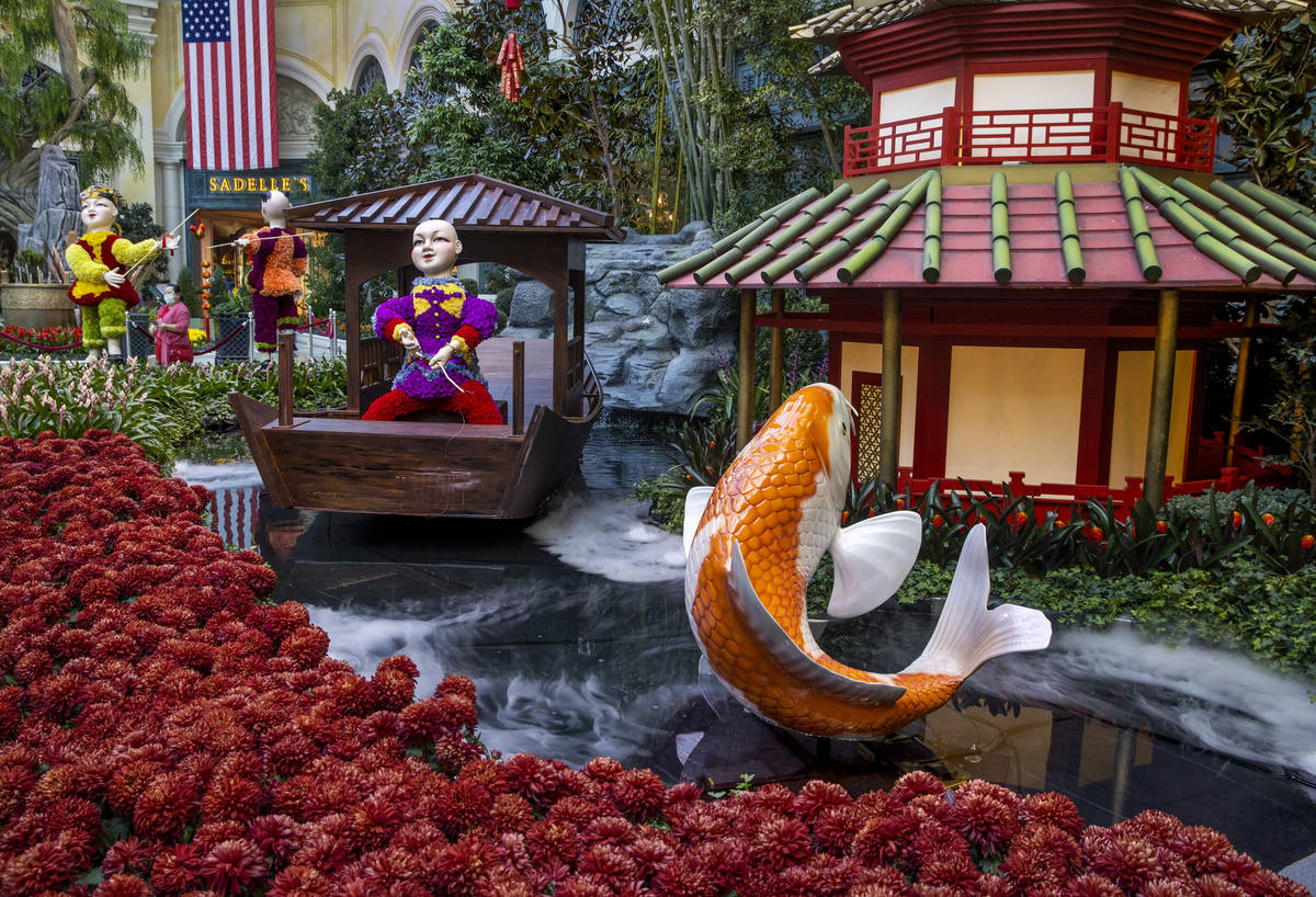 Smoke rises from the pond about a koi and flower-covered fishermen as the Bellagio Conservatory ...