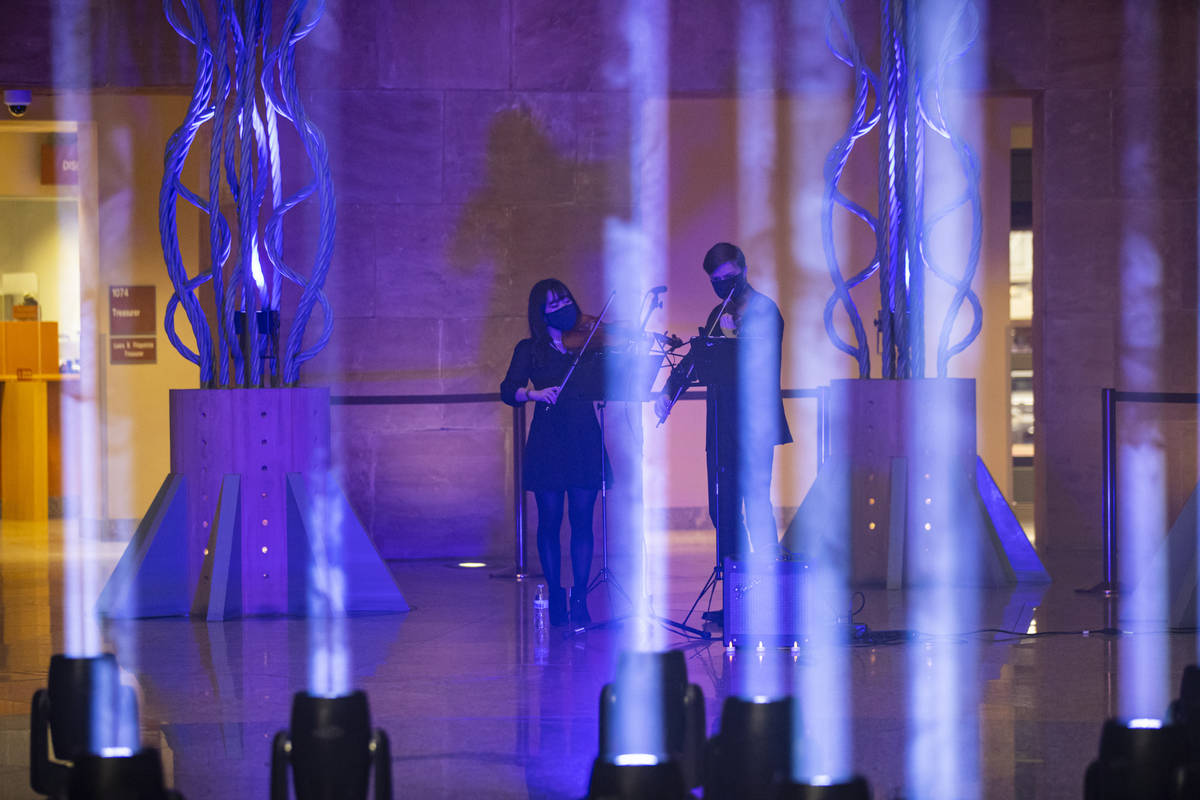 Violinists Wonyoung Na, left, and Dmytro Nehrych perform as 29 lights illuminate the rotunda at ...