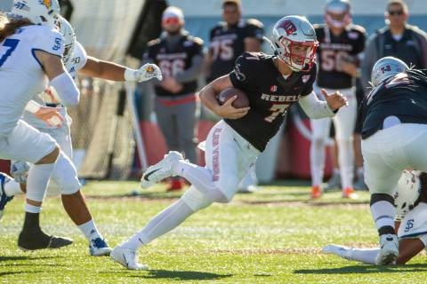 UNLV Rebels quarterback Kenyon Oblad (7) cuts up field through the San Jose State Spartans defe ...