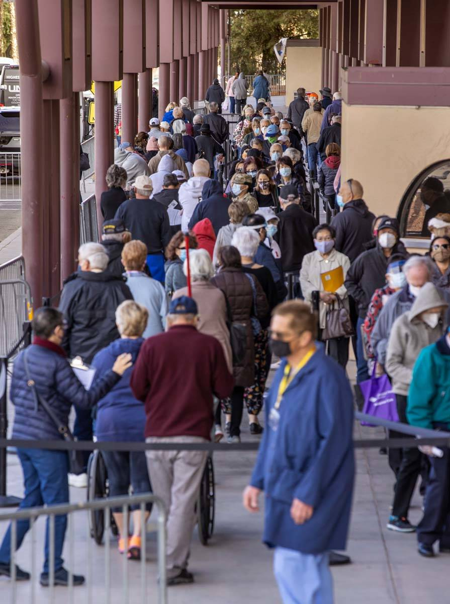 People move along while weaving in line to enter the Cashman Center for COVID-19 vaccinations o ...