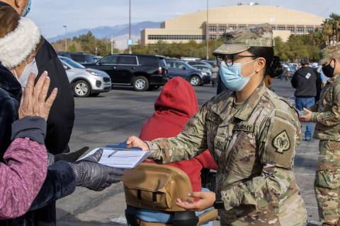 PFC Wendy Garcia passes out paperwork as people wait in line to enter the Cashman Center for CO ...