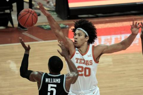 Texas' Jericho Sims (20) blocks a pass by Kansas State's Rudi Williams (5) during the first hal ...