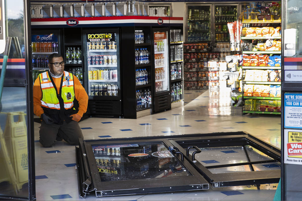A worker surveys damage after a man who got into an argument with a convenience store clerk dro ...