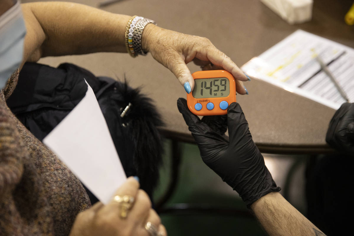 Lynne Lober, 70, receives a 15-minute timer after receiving the COVID-19 vaccine from Nathan Va ...