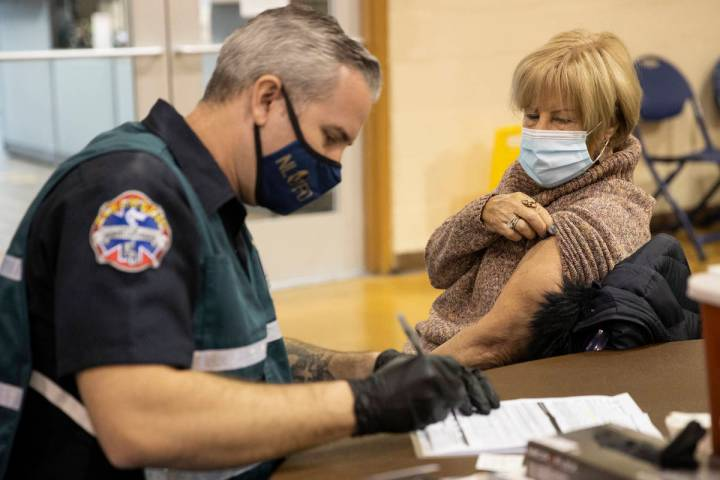 Lynne Lober, 70, waits to receive the COVID-19 vaccine from Nathan Van Wingerden, paramedic for ...