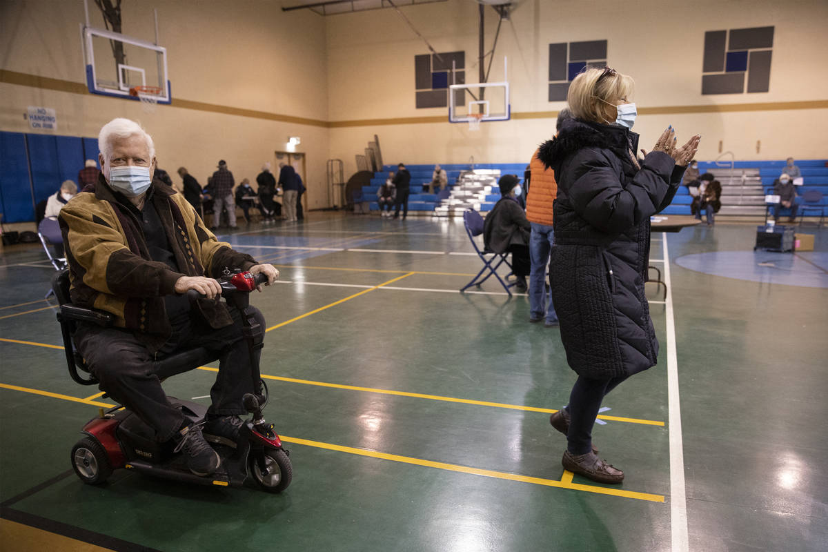 Richard Lober, left, 79, and his wife Lynne, 70, get in line to receive the COVID-19 vaccine at ...