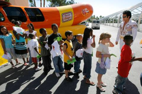 A group of children wait in line with Elvis impersonator Johnny Thompson, right, for hot dogs a ...
