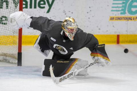 Golden Knights goaltender Logan Thompson (36) makes an acrobatic save during practice at City N ...