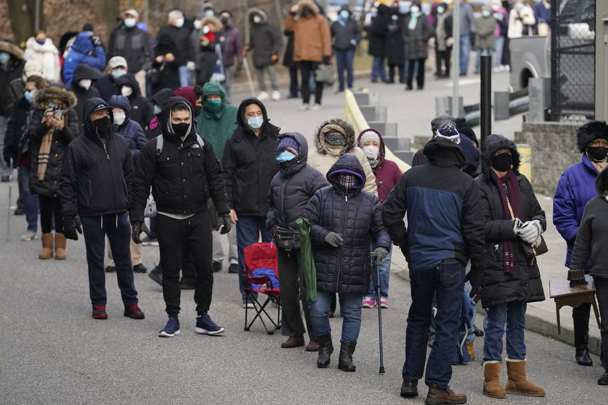 People wait in line for the COVID-19 vaccine in Paterson, N.J., Thursday, Jan. 21, 2021. The fi ...