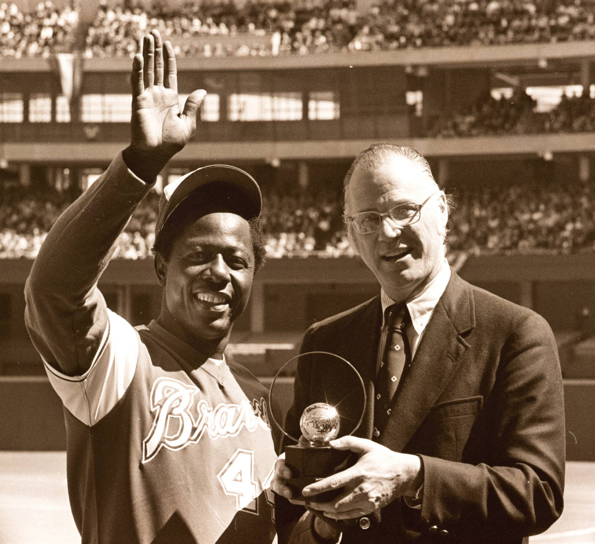 FILE - In this April 4, 1974, file photo, baseball commissioner Bowie Kuhn, right, presents Atl ...