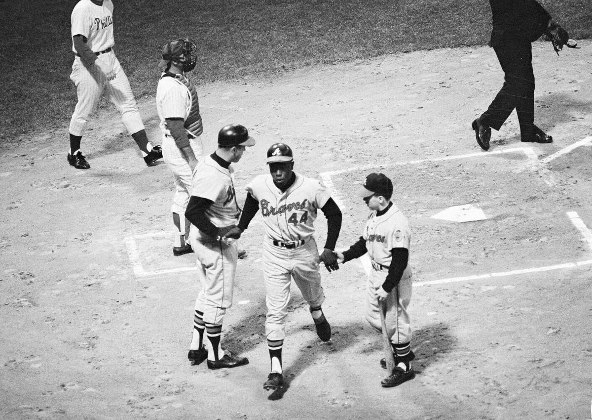 Hank Aaron of the Atlanta Braves is congratulated near home plate by Eddie Mathews and the Brav ...