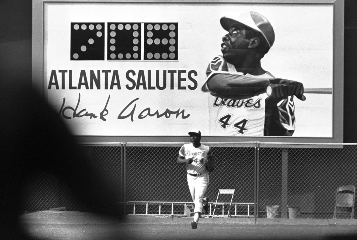 A new sign showing the number of Hank Aaron's home runs provides a background as he runs off th ...