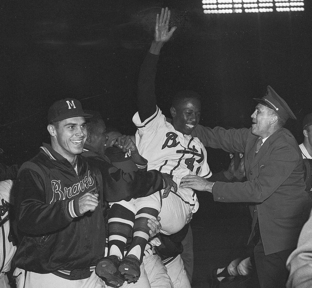 Milwaukee Braves' Hank Aaron is carried from the baseball field Sept. 23, 1957, by teammates af ...