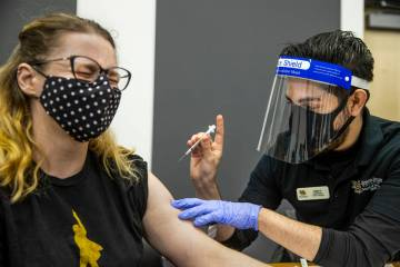 Medical worker Jennifer Gorden, left, winces a little as Nevada State College School of Nursing ...