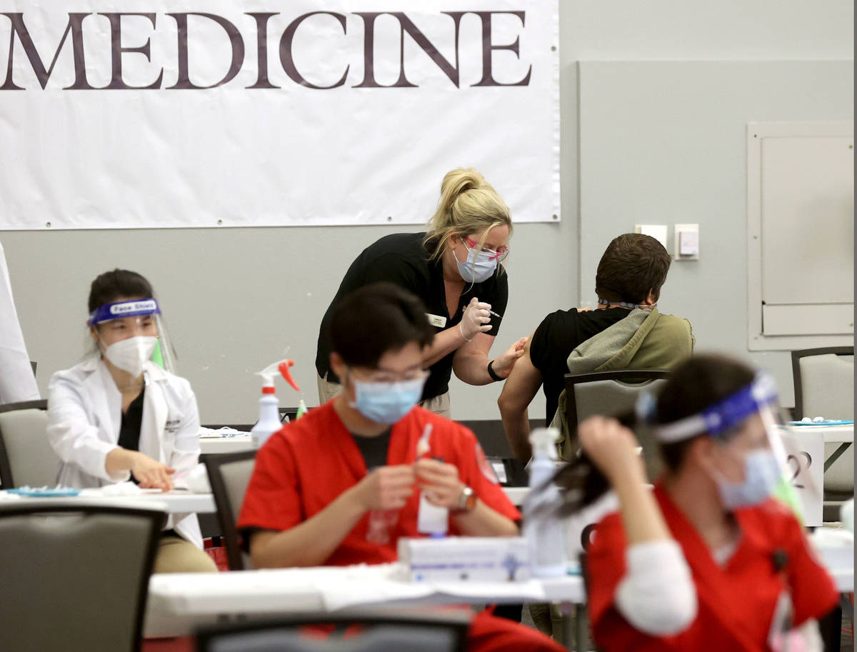 Lindsay Rosenberg, rear, a Nevada State College nursing student, gives a COVID-19 vaccine durin ...