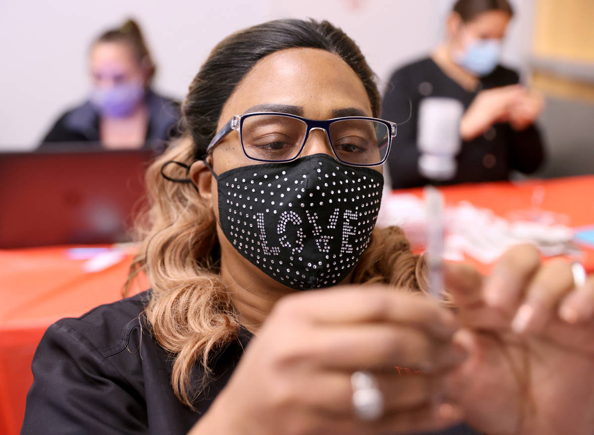 Certified Medical Assistant Angela Woods prepares a COVID-19 vaccine during a UNLV Medicine cli ...