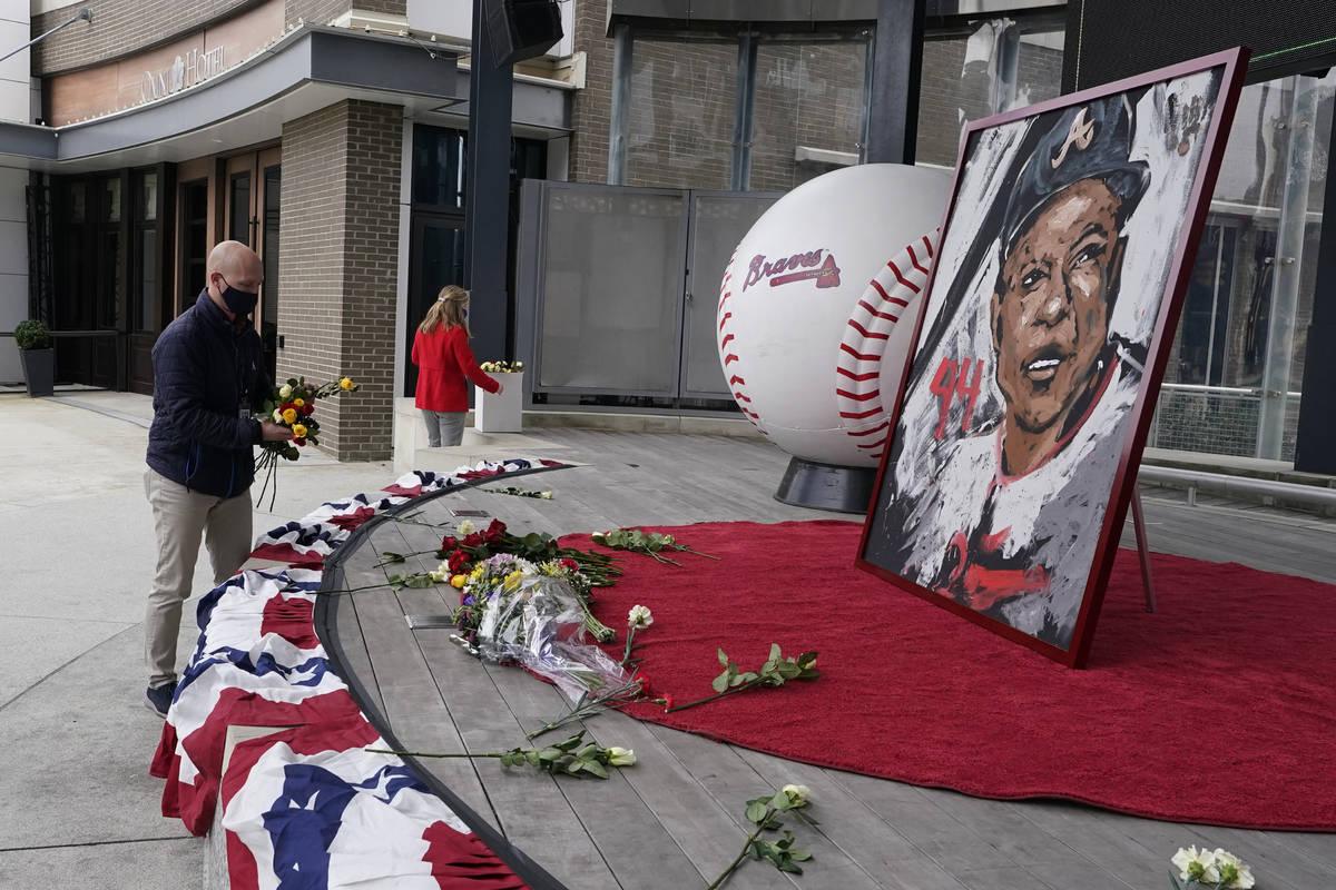 Atlanta Braves employees place flowers next to a portrait Atlanta Braves' Hank Aaron outside Tr ...