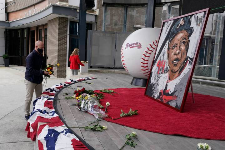 Atlanta Braves employees place flowers next to a portrait Atlanta Braves' Hank Aaron outside Tr ...