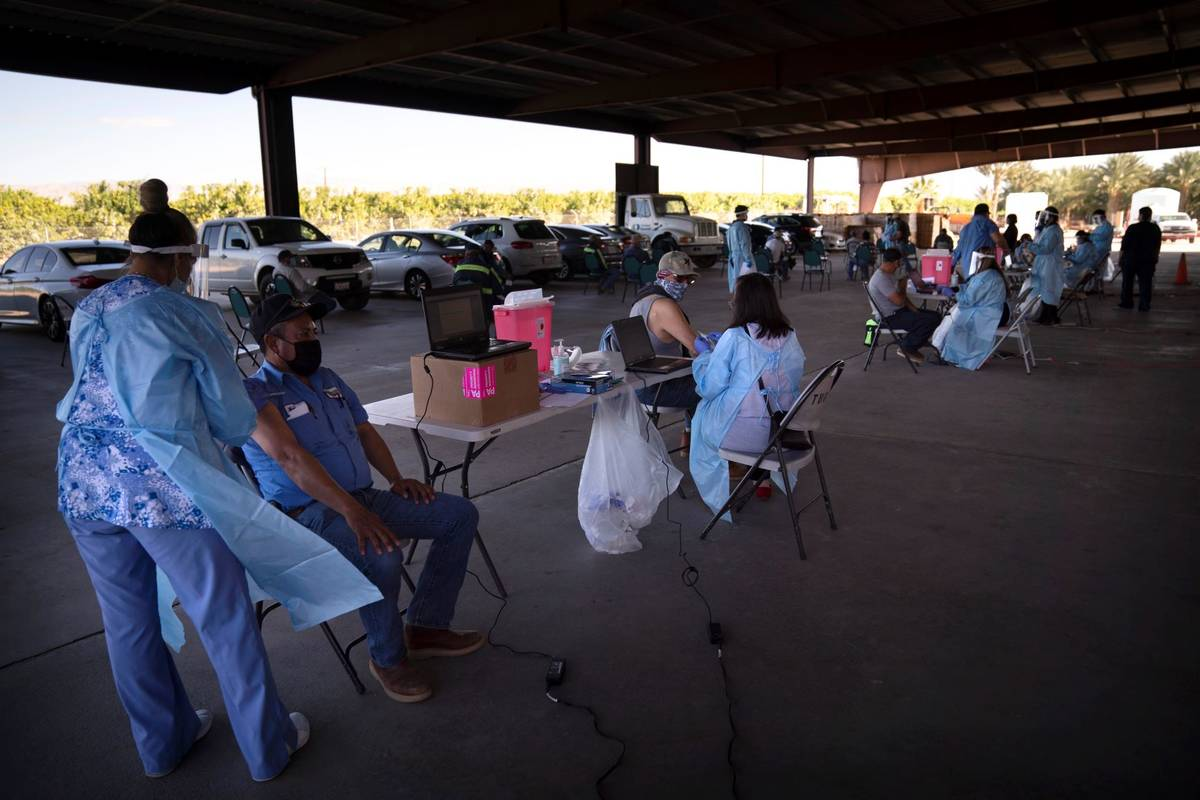 Farm workers receive the Pfizer-BioNTech COVID-19 vaccine at Tudor Ranch in Mecca, Calif., in J ...