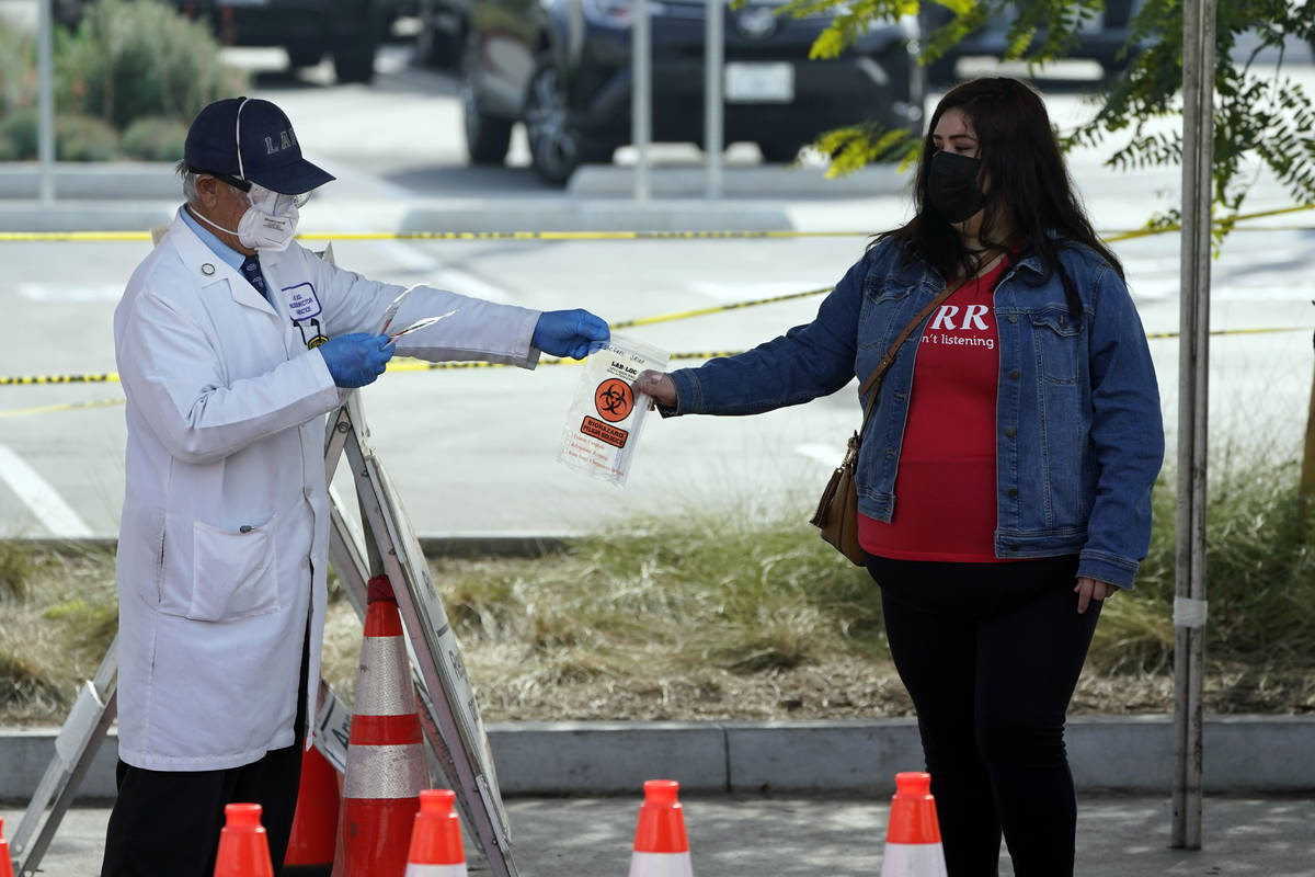 FILE - In this Jan. 7, 2021, file photo, a technician distributes a test kit at a COVID-19 walk ...