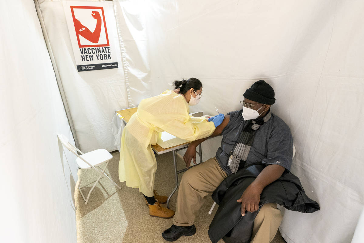 In a Jan. 23, 2021, file photo, registered Nurse Shyun Lin gives Roberto Fisher, 72, the first ...