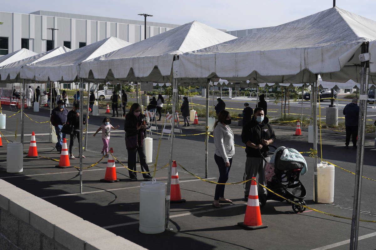 FILE - In this Jan. 7, 2021, file photo, people line up at a COVID-19 walk-up testing site on t ...