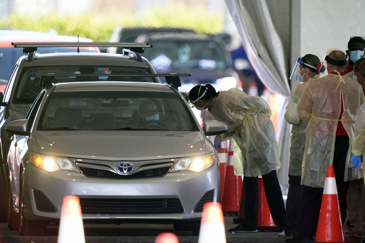 FILE - In this Jan. 6, 2021, file photo, health care workers prepare to inoculate a driver at a ...