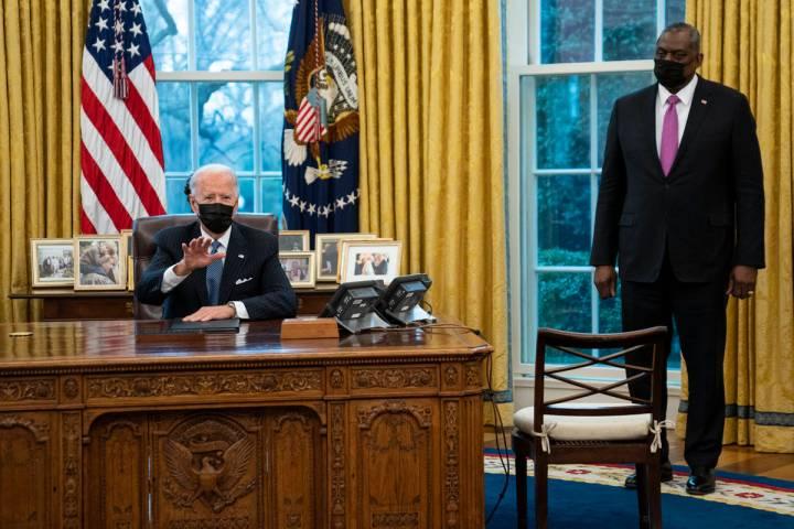 Secretary of Defense Lloyd Austin listens as President Joe Biden speaks before signing an Execu ...