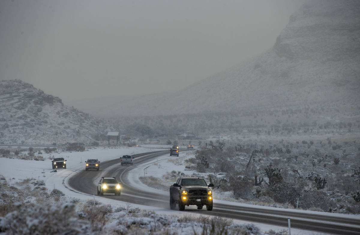 Cars navigate the snowy road in the Red Rock Conservation Area on Tuesday, Jan. 26, 2021, in La ...