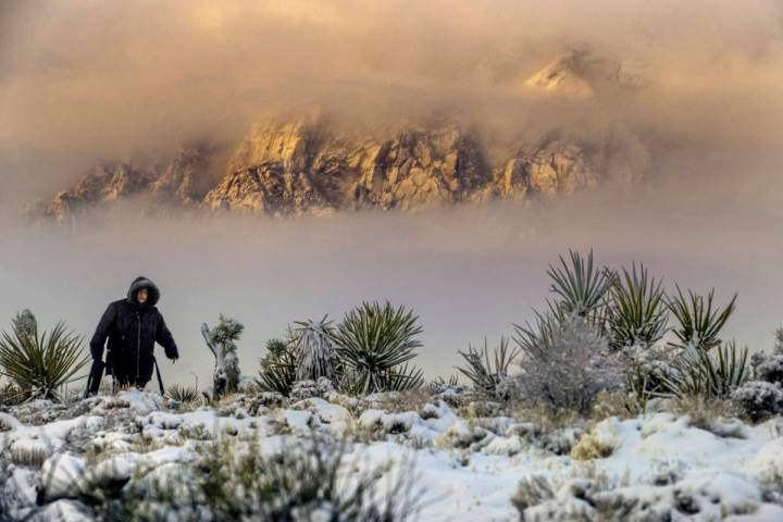 Sylvia Hinojosa hikes up to the overlook as the clouds break on a snowy day in the Red Rock Con ...