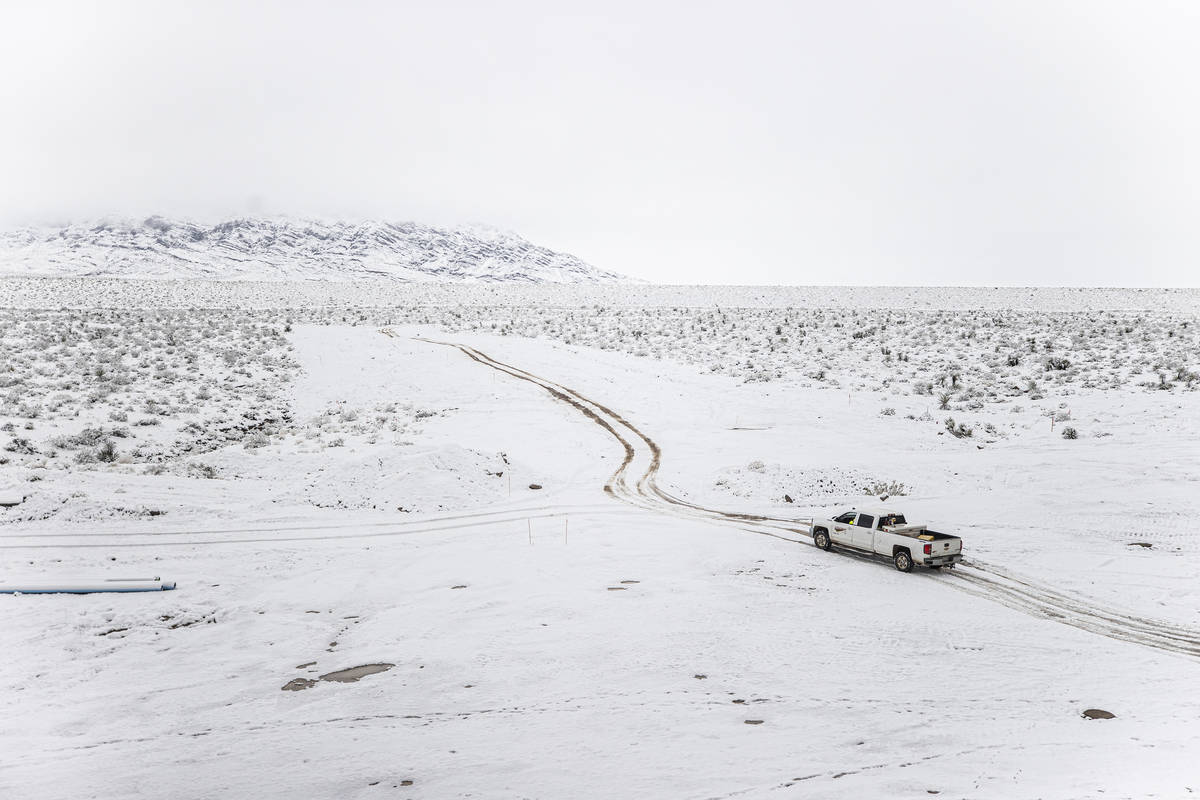 A truck makes its way through the snow at a construction sight in northwest Las Vegas on Tuesda ...