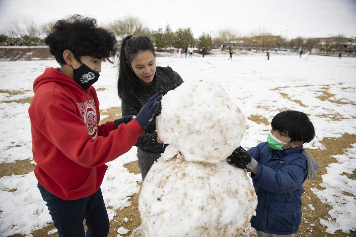 Jenny Lyn Hilario, center, with her sons Gabriel, 12, left, and Isaac, 7, build a snowman at Hu ...